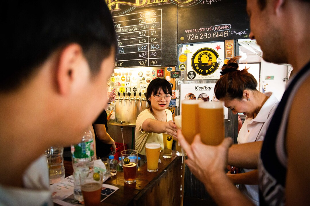 A bartender serves patrons at Chit Beer in Thailand