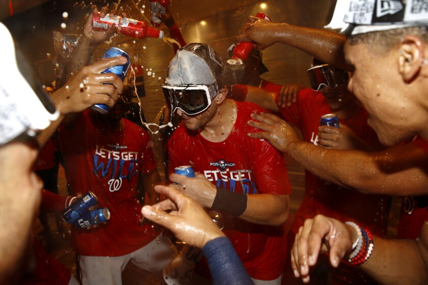 Washington Nationals shortstop Trea Turner, center, celebrates with teammates after the second baseball game of a doubleheader against the Philadelphia Phillies, Tuesday, Sept. 24, 2019, in Washington. Washington won 6-5 and clinched a Wild Card berth. (AP Photo/Patrick Semansky)
