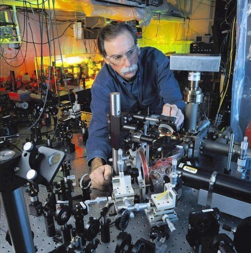 David J. Wineland of the National Institute of Standards and Technology adjusts an ultraviolet laser beam used to manipulate ions in a high-vacuum apparatus containing an ion trap. The device demonstrates the basic operations required to create a powerful quantum computer.