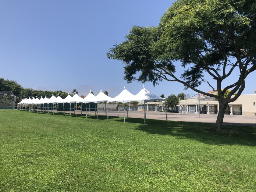 White tents on a grass field