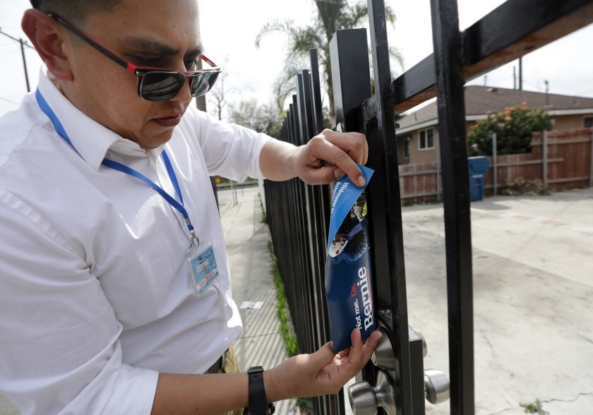 Ricardo Alonzo Ugalde places a flier on a gate while canvassing for Bernie Sanders in East Los Angeles in February