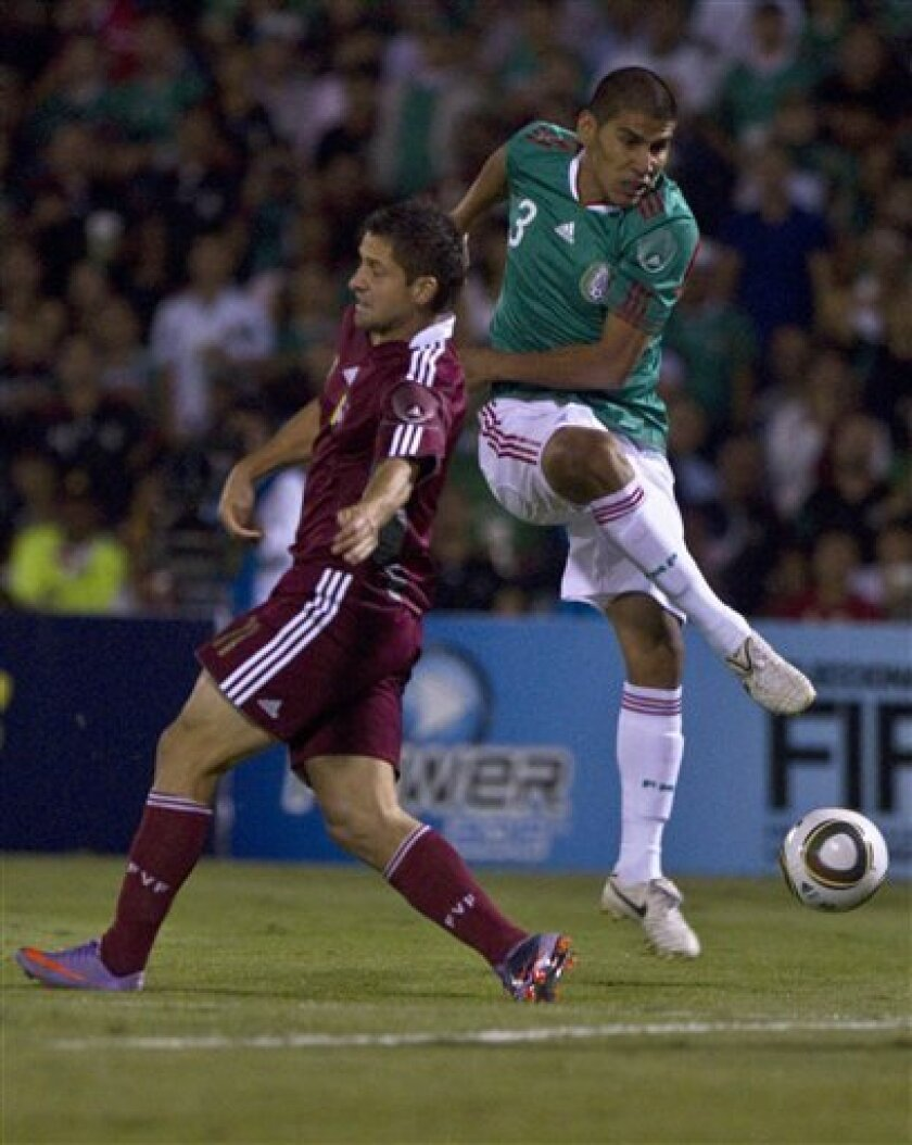 Mexico's Carlos Salcido, right, fights for the ball with Venezuela's goalie Cesar Gonzalez during a friendly soccer match at the Benito Juarez stadium in Ciudad Juarez, Mexico, Tuesday, Oct. 12, 2010. (AP Photo/Guillermo Arias)