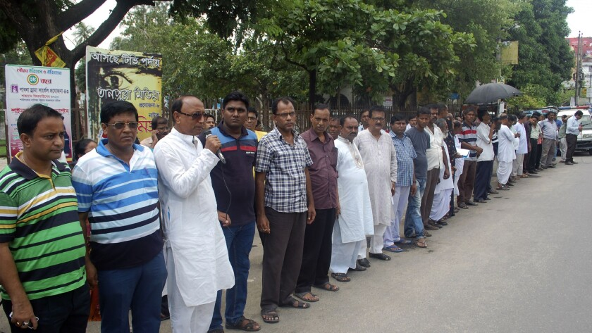 Men form a human chain to protest the killing of a Hindu man in Pabna.