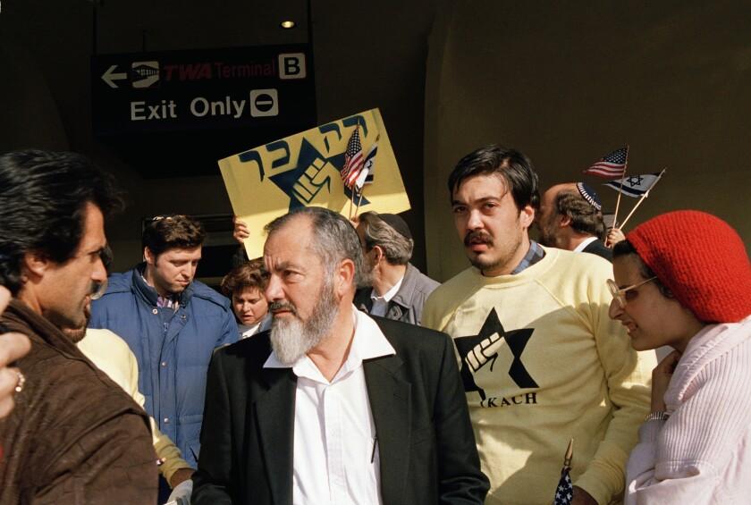 El rabino ultraderechista Meir Kahane (centro) a su llegada al aeropuerto John F. Kennedy de Nueva York el 27 de octubre de 1988. Su violenta ideología antiárabe sigue viva en Israel. (AP Photo/Susan Ragan, File)