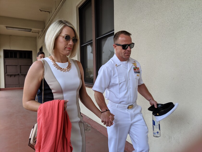 Navy SEAL Edward Gallagher and his wife Andrea Gallagher arrive at the court house Tuesday before his court martial trial. Gallagher has pleaded not guilty to war crimes charges.