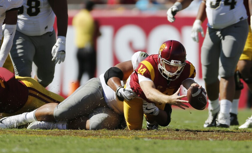 Running a quarterback keeper, USC's Sam Darnold (14) stretches as he is brought down by Colorado defensive end Jordan Carrell in the first half Saturday.