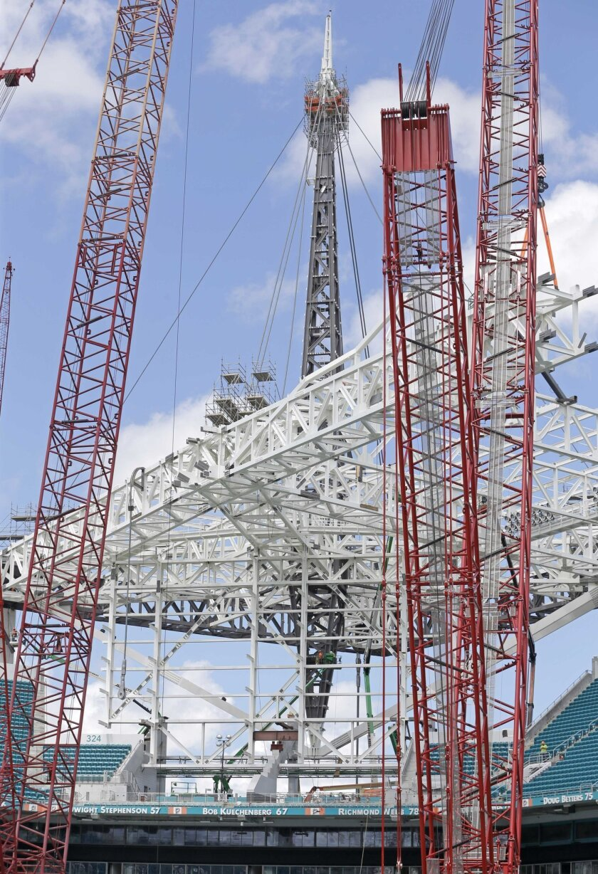 Cranes work on the structural support of one of four spires that will be 200 feet above the roof surface and 357 feet from the ground at the Miami Dolphins' NFL football stadium, Thursday, June 2, 2016, in Miami Gardens, Fla. Construction crews are working around the clock to complete the latest ph