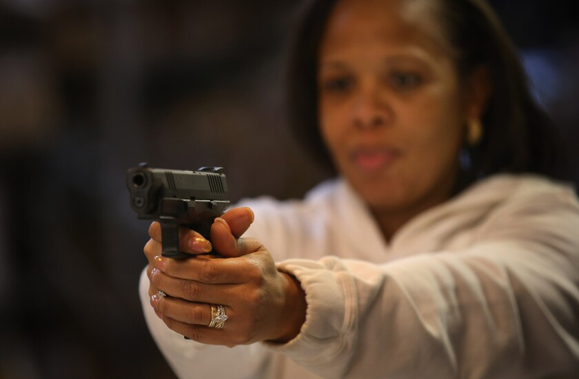 Cheryl Bourgeois learns how to fire a pistol during an NRA Basic Pistol Course at Freddie Bear Sports sporting goods store in Tinley Park, Ill.