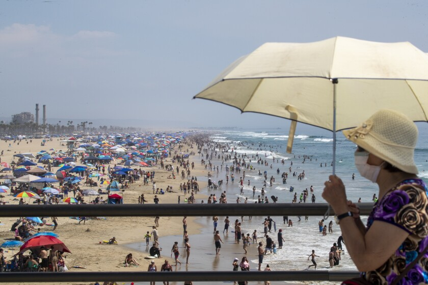 A woman holds an umbrella with a crowded beach in the background