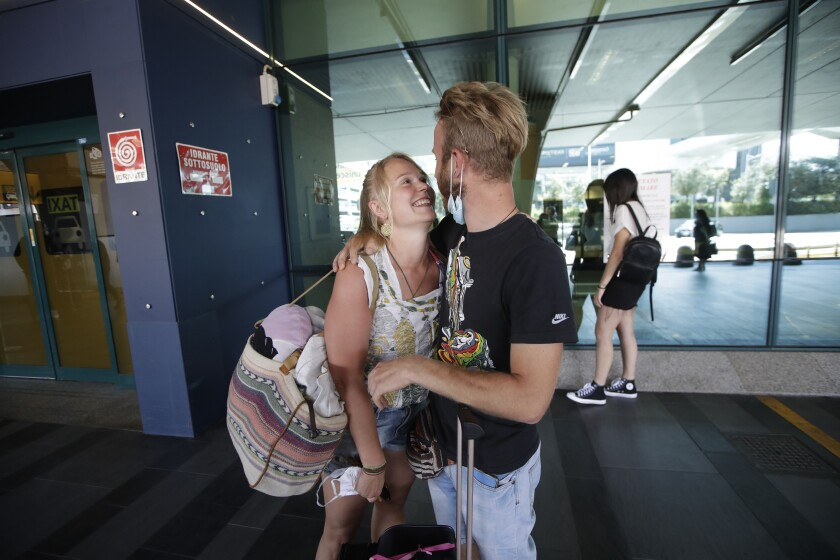 Andrea Monti hugs his girlfriend Katherina Scherf who just arrived from Duesseldorf, Germany at Rome's Fiumicino airport, Wednesday, June 3, 2020. Rome's Fiumicino airport sprang back to life on Wednesday as Italy opened regional and international borders in the final phase of easing its long coronavirus lockdown, allowing families and loved ones separated by the global pandemic to finally reunite. (AP Photo/Alessandra Tarantino)