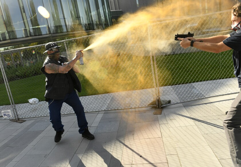 A man in a U.S. flag mask sprays Mace at a person pointing a handgun at him