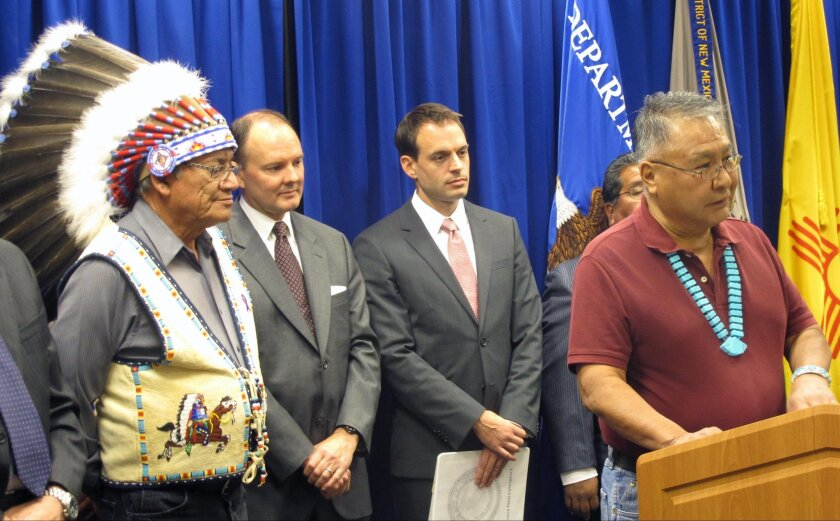 Ramah Navajo Chapter President David Jose, right, is surrounded by federal and tribal officials as he speaks about a $940 million settlement with the federal government during a news conference at the U.S. Attorney's Office in Albuquerque, N.M., on Thursday, Sept. 17, 2015. The settlement stems from a decades-old claim that the government failed to adequately compensate tribes while they managed education, law enforcement and other federal services. (AP Photo/Mary Hudetz)