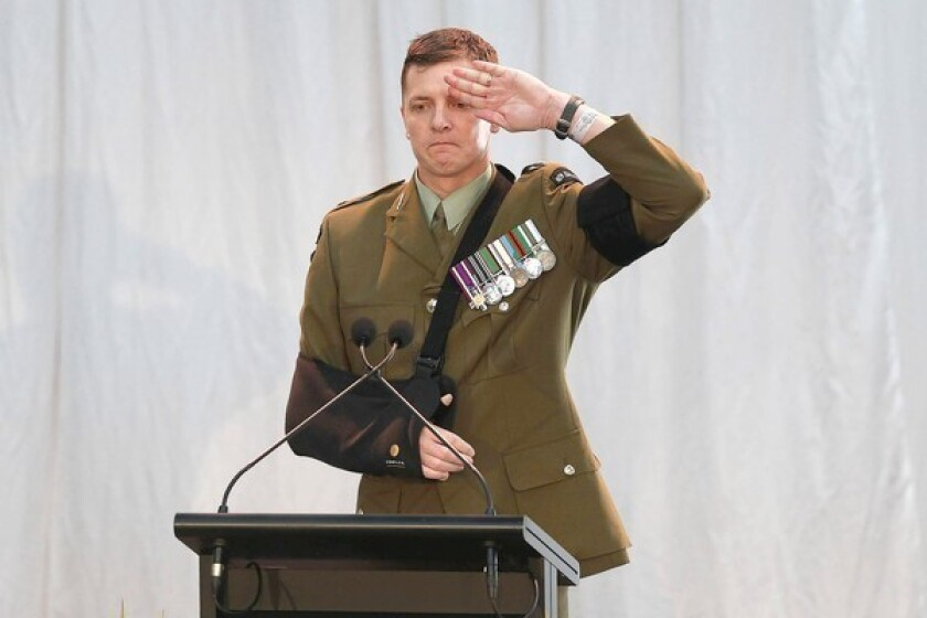 Maj. Craig Wilson pays his respects during a memorial service in Christchurch, New Zealand, for three soldiers killed in Bamiyan province, Afghanistan. New Zealand is expected to pull its troops out of the country early next year, six months ahead of schedule.