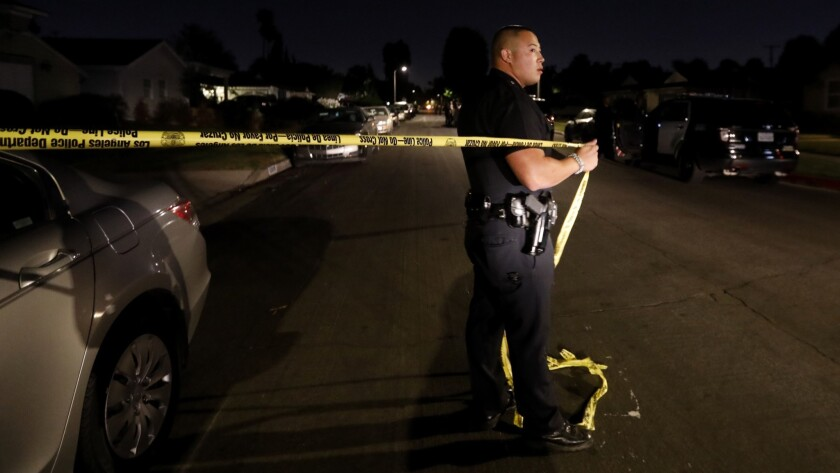NORTH HOLLYWOOD, CA JUNE 10, 2018: LAPD Officer Moberg moves the yellow crime tape as a LAPD vehi