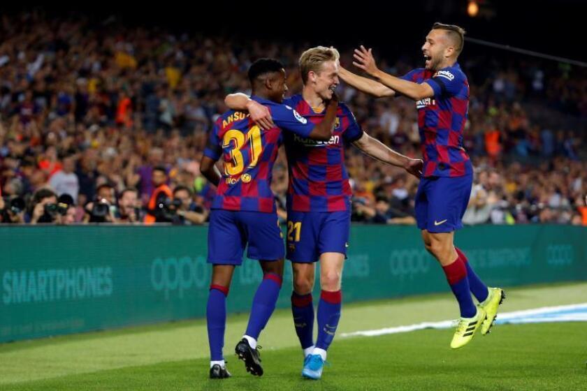 El centrocampista holandés del FC Barcelona Frenkie de Jong celebra con Jordi Alba (d) y Ansu Fati (i) tras marcar el segundo gol ante el Valencia, durante el partido de la cuarta jornada de Liga en Primera División que disputaron en el estadio Camp Nou, en Barcelona. EFE/Toni Albir