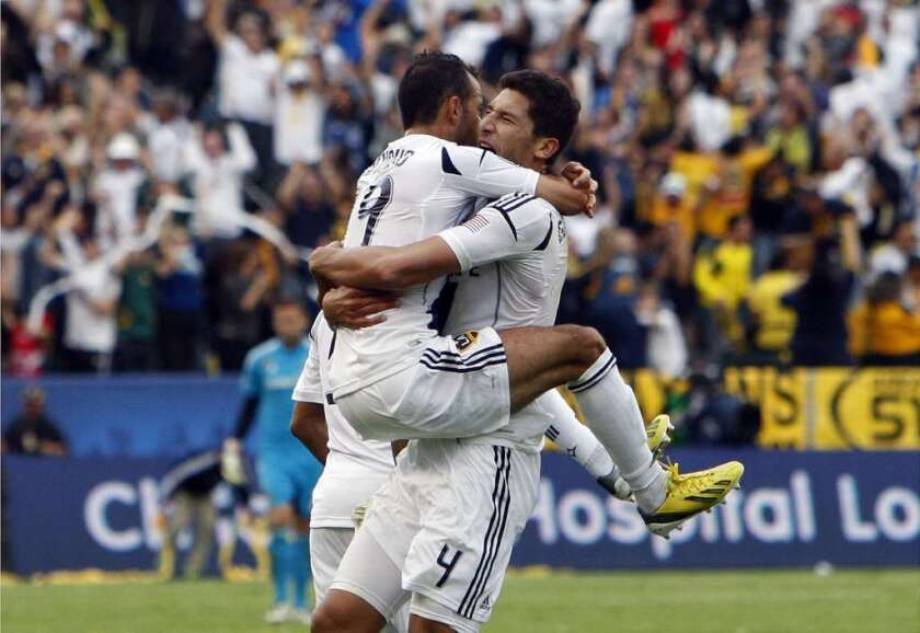 The Galaxy's Juninho leaps into the arms of Omar Gonzalez during the MLS Championship against the Houston Dynamo.