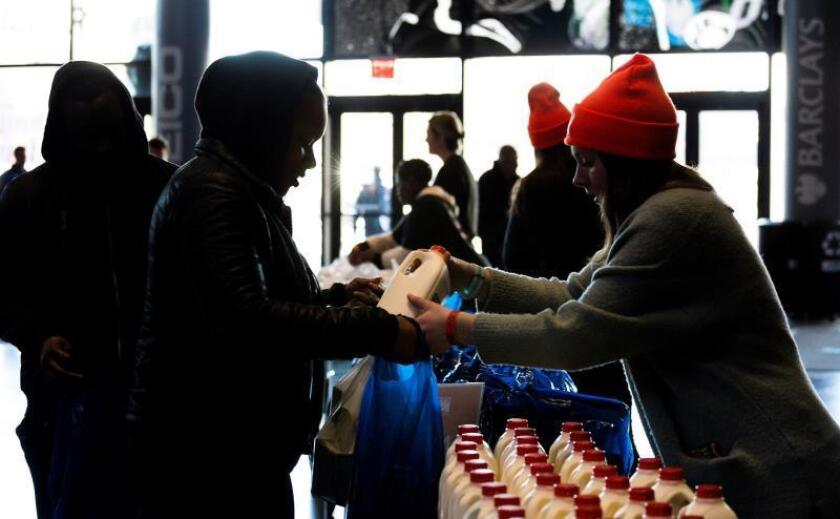 People pick up free food at a food distribution center on Jan. 22, 2019, in New York City amid the crisis for many federal workers who have not received paychecks for more than a month due to the partial US government shutdown. EFE-EPA/ Justin Lane