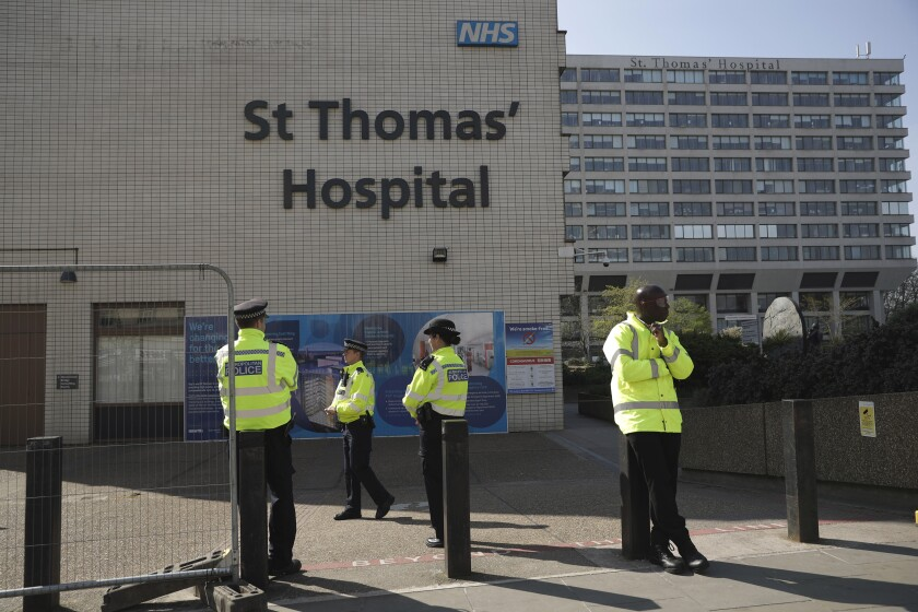 Three police officers at left and a security guard at right guard an entrance outside St Thomas' Hospital in London, where British Prime Minister Boris Johnson was being treated for coronavirus, Friday, April 10, 2020.