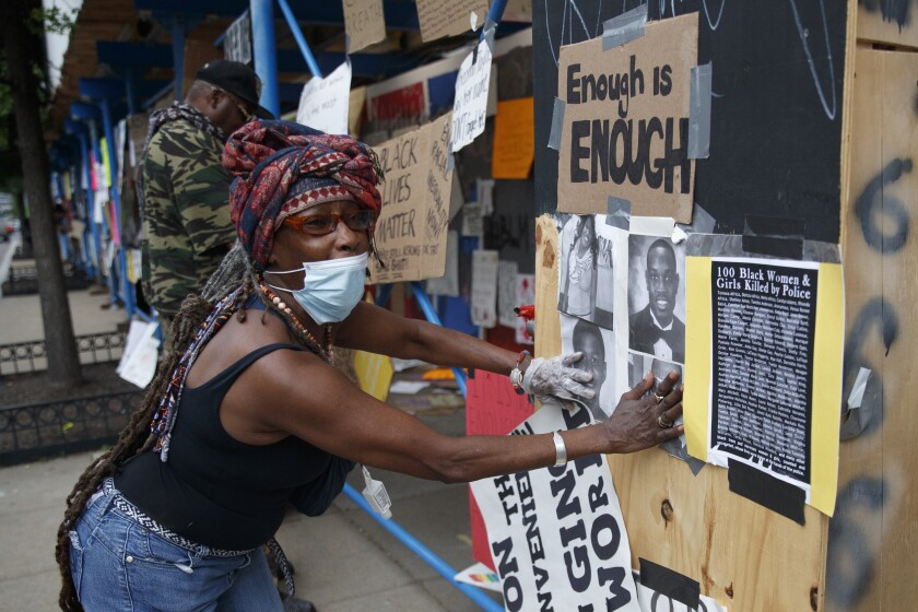 Sister Mamie reposts signs that were removed form the Lafayette Park parameter fence at the site of protests, Wednesday, June 10, 2020, near the White House in Washington. The protests began over the death of George Floyd, a black man who was in police custody in Minneapolis. Floyd died after being restrained by Minneapolis police officers. (AP Photo/Carolyn Kaster)
