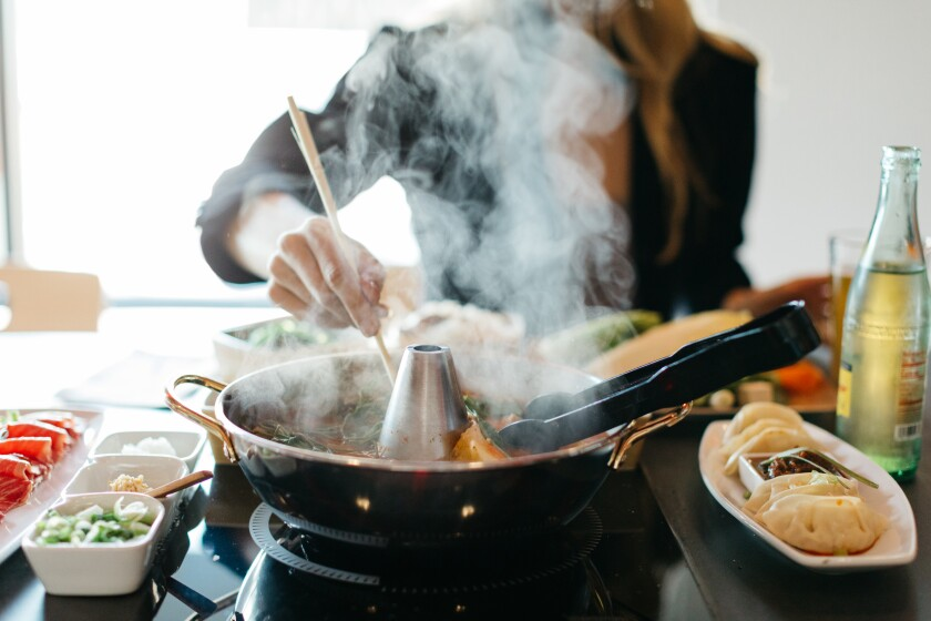 People cook their own food at Tabu Shabu restaurant in Carlsbad