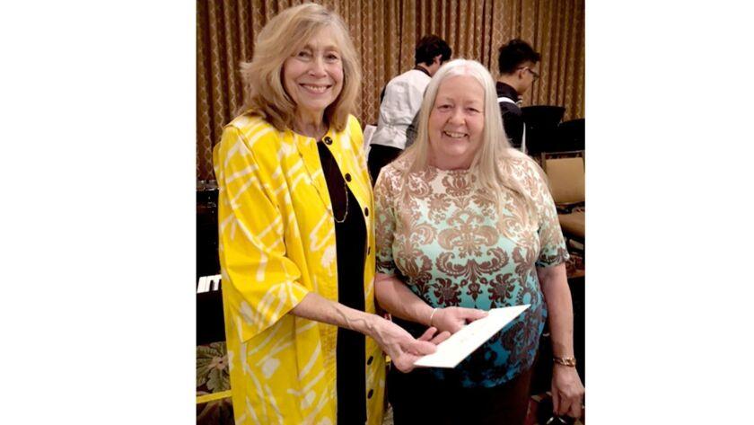 Glendale Philharmonic co-president Stella Balesh presents raffle prize winner Kay Hostetler with box
