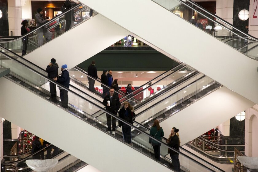 FILE - In this Friday, Nov. 29, 2013, file photo, shoppers ride escalators between floors during Black Friday shopping at Macy's, in Chicago. The Federal Reserve reports how much consumers borrowed in November on Wednesday, Jan. 8, 2014. (AP Photo/Andrew A. Nelles, File)
