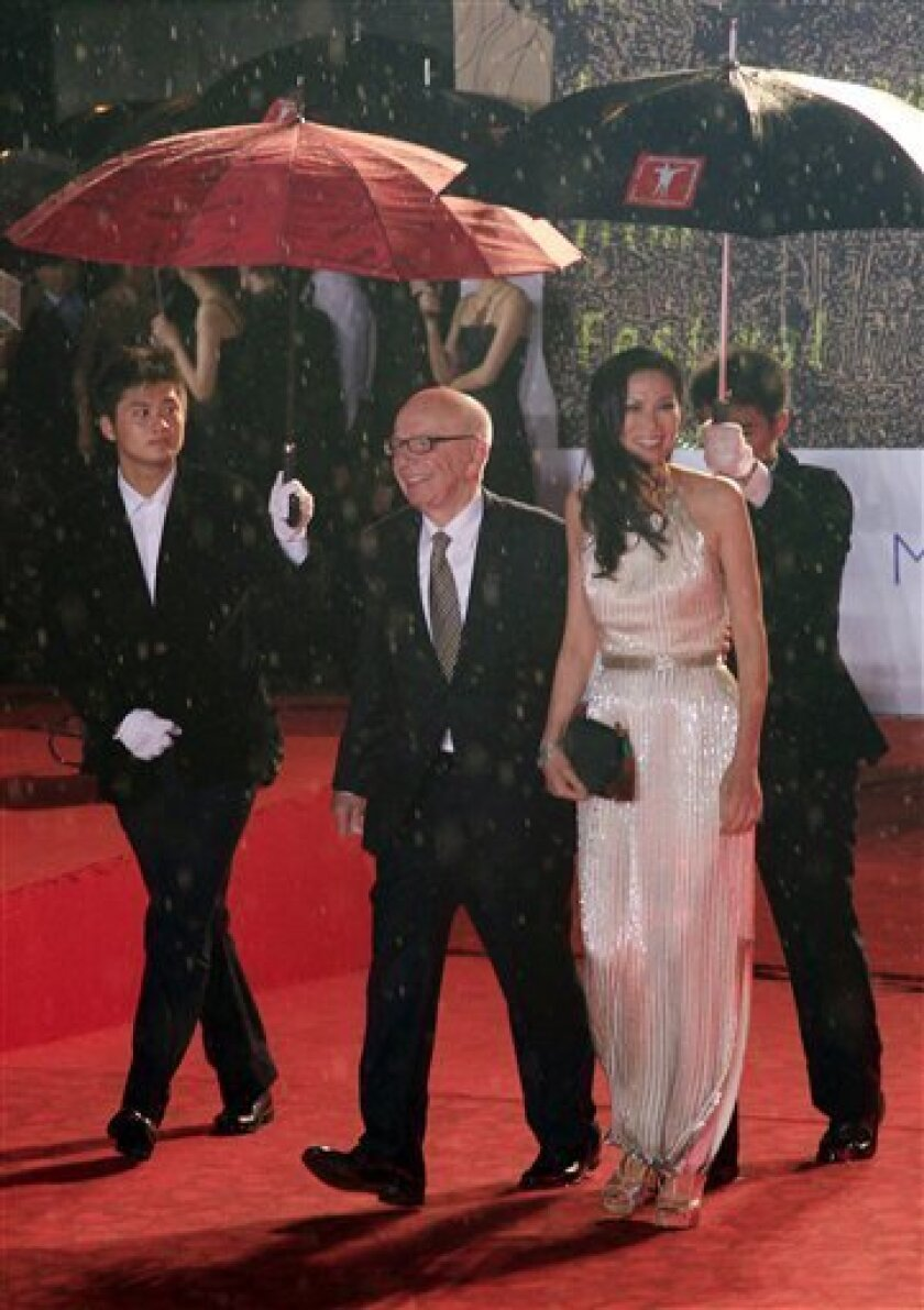 Rupert Murdoch, 2nd left, and his wife Wendi Deng, 2nd right, walk on the red carpet prior to the opening ceremony of the Shanghai International Film Festival at Shanghai Grand Theater Saturday June 11, 2011 in Shanghai. (AP Photo/Eugene Hoshiko)