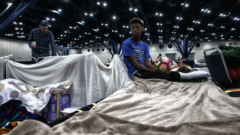 Travis Smith, 14, rests on a cot where his family sleeps at the George R. Brown Convention Center, w