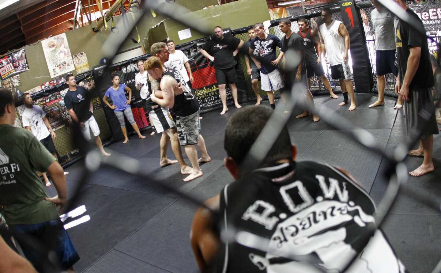 War veterans gather in a circle inside a fight cage as Todd Vance demonstrates an offensive martial arts move. The workouts help veterans cope with post-traumatic stress issues and have been endorsed by psychologists.