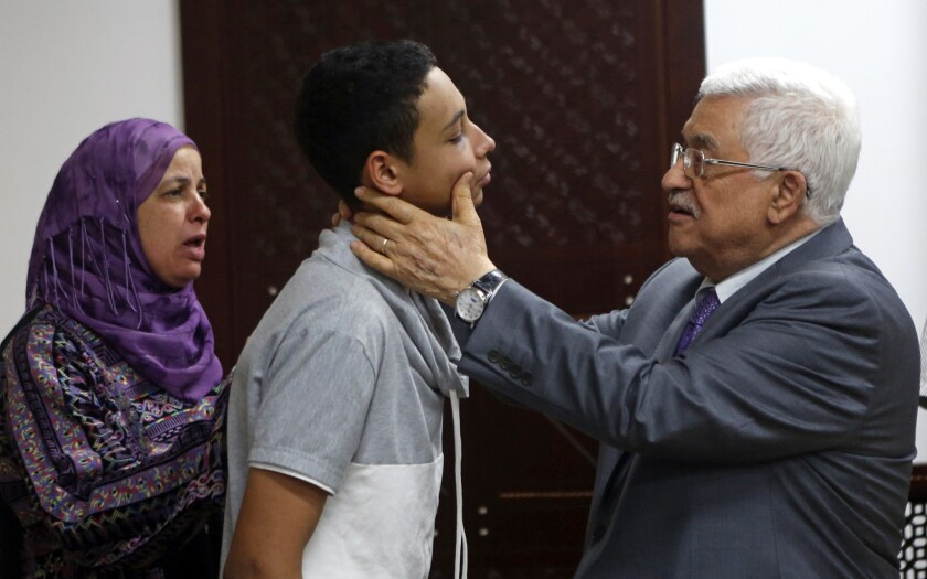 Palestinian Authority President Mahmoud Abbas examines the injuries of Palestinian American teen Tariq Abukhdeir during a meeting on July 7.