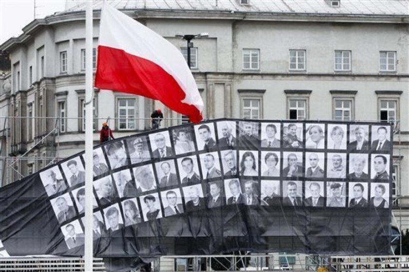 Workers prepare a poster with photos of the victims of a plane crash at Pilsudski square in Warsaw, Friday, April 16, 2010.  Polish President Lech Kaczynski who was killed in a plane crash in Russia is going to be buried in Krakow on Sunday. On Saturday a commemoration ceremony is planned at Pilsud