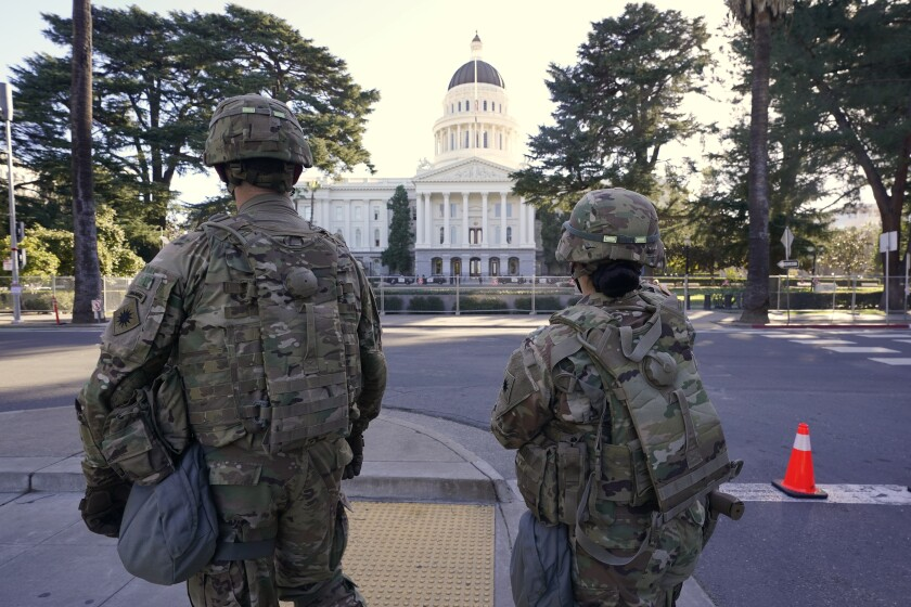 Members of the California National Guard walk past the state Capitol in Sacramento
