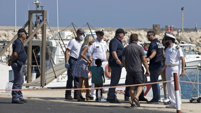 Migrant women and children are assisted by medical staff and law enforcement officers after disembarking from an Italian Coast Guard ship in the port of Pozzallo on Sunday.