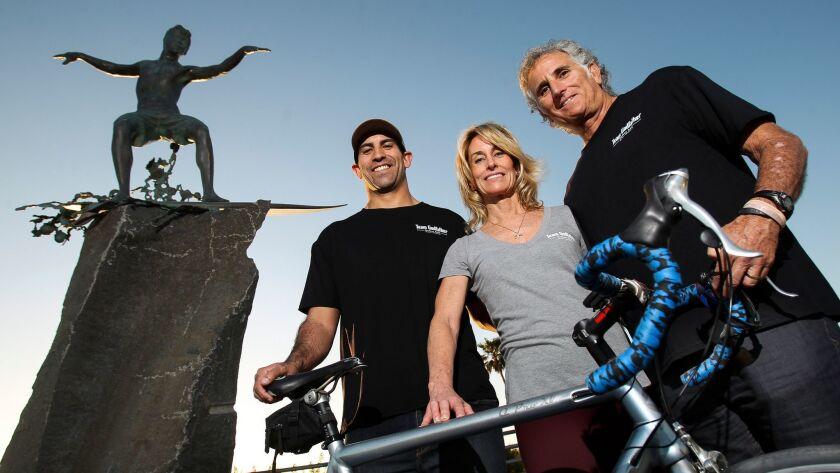 Team Godfather chairman Greg Sacks, right, with board members Michael Ramirez Jr. and Maureen Ramirez at the Cardiff Kook statue in Encinitas. The charity's Bike4Mike ALS fundraiser is named for the late Mike Ramirez of Carlsbad.