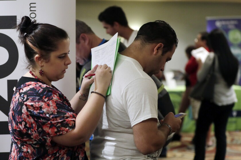 In this Jan. 30, 2018 photo, Loredana Gonzalez, of Doral, Fla., fills out a job application at a JobNewsUSA job fair in Miami Lakes, Fla. On Friday, March 9, 2018, the Labor Department reports on job openings and labor turnover for January.