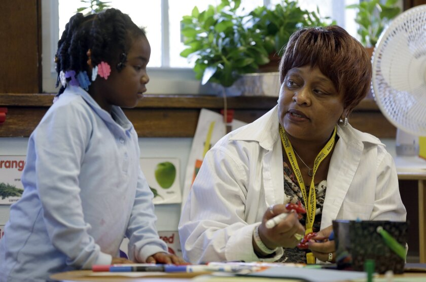 In this photo taken Wednesday, Nov. 13, 2013, Elmira Warren talks with  Camil Douthit, 5, a student in Warren's pre-school class at Clay Elementary Community Education school in St. Louis. Warren is a participant in a pilot program called Home Works that sends public school teachers into their stud