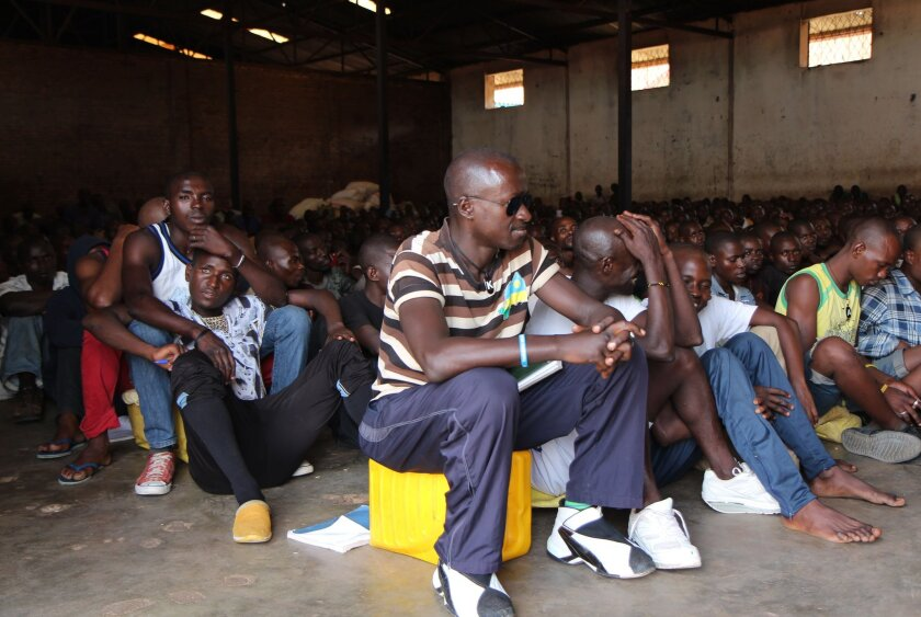 """Men sit in the Gikondo Transit Center in Kigali on Sept. 24. A Human Rights Watch report released during the day accused Rwanda of rounding up """"undesirables,"""" including beggars and prostitutes, and holding them in the grim center."""