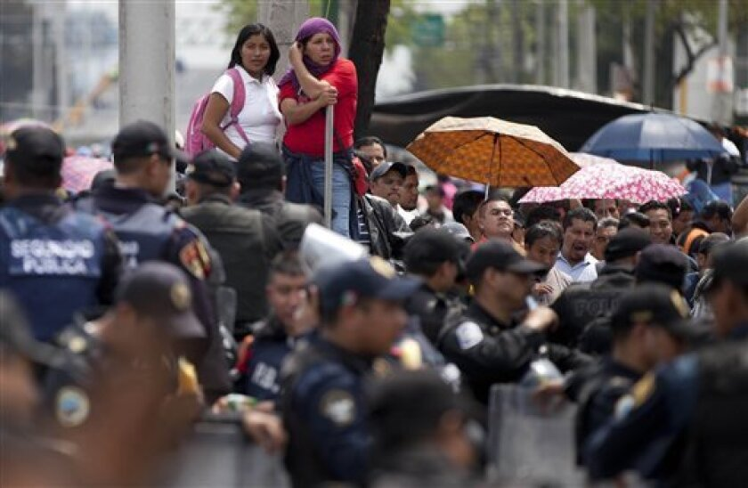 Striking teachers block a road near the Benito Juarez International Airport as police stand guard in Mexico City, Thursday, Sept. 5, 2013. Teachers angry over the passage of a national education reform partially blocked the main approach to the airport, forcing many passengers to leave their cars and rush through the streets on foot to catch their flights. (AP Photo/Eduardo Verdugo)