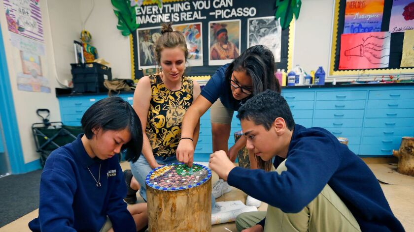 Isabel Halpern, a teaching artist with ArtReach, helps students Hannah Castaneda, left, Lizeth Gutierrez, and Dominick Aguilar with a mosaic project at O'Farrell Charter School in Skyline.