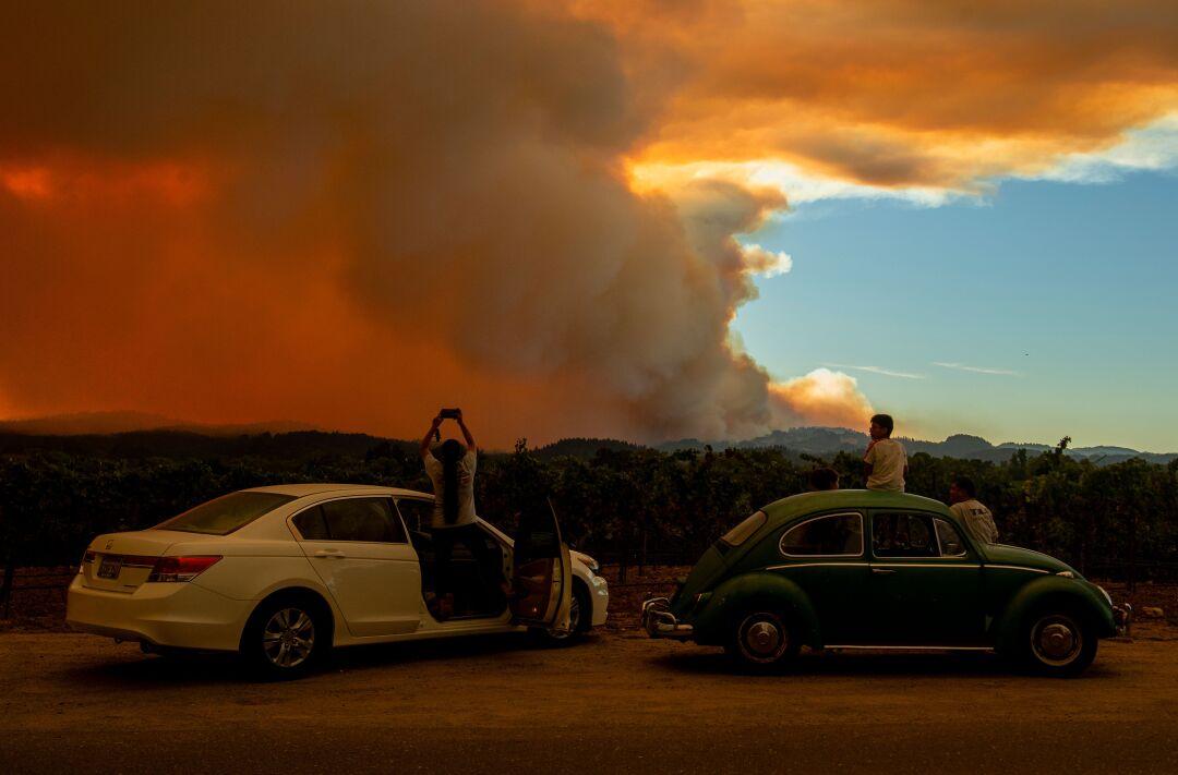 People watch a wildfire in Healdsburg, Calif.
