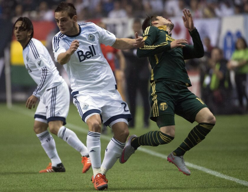 Vancouver Whitecaps FC Octavio Rivero, left, fights for control of the ball with Jorge Villafana, right, of the Portland Timbers during the second half of MLS soccer action in Vancouver, British Columbia, Sunday, Nov. 8, 2015. (Jonathan Hayward/The Canadian Press via AP)