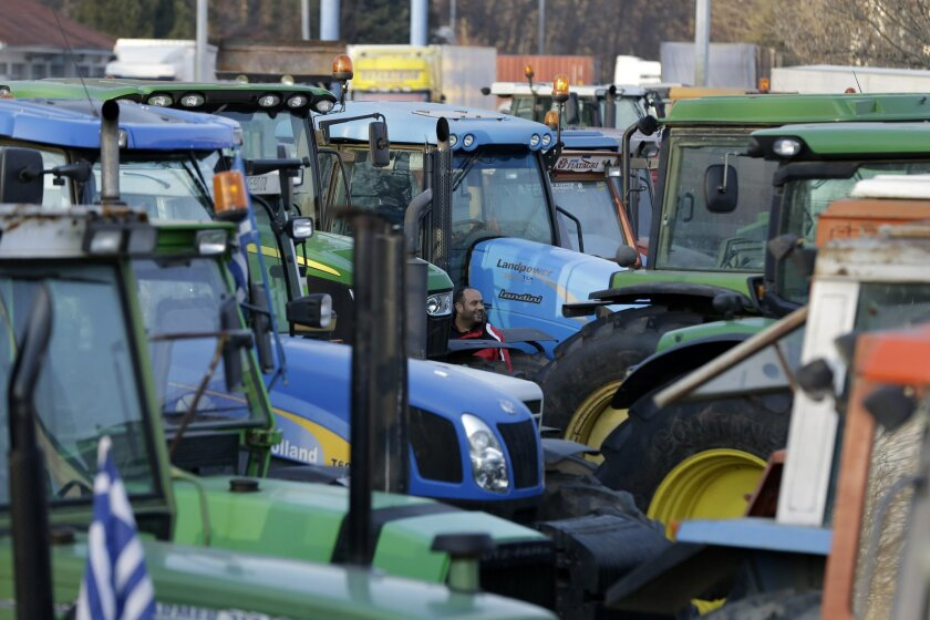 A protesting farmer walks between parked tractors in the northern Greek village of Promachonas village at the customs of the Greek-Bulgarian borderline on Thursday, Jan. 21, 2016. Farmers are preparing to use their tractors to block key highways in Greece, to protest drastic new income cuts under planned pension reforms by the radical left-led government. (AP Photo/Thanassis Stavrakis)