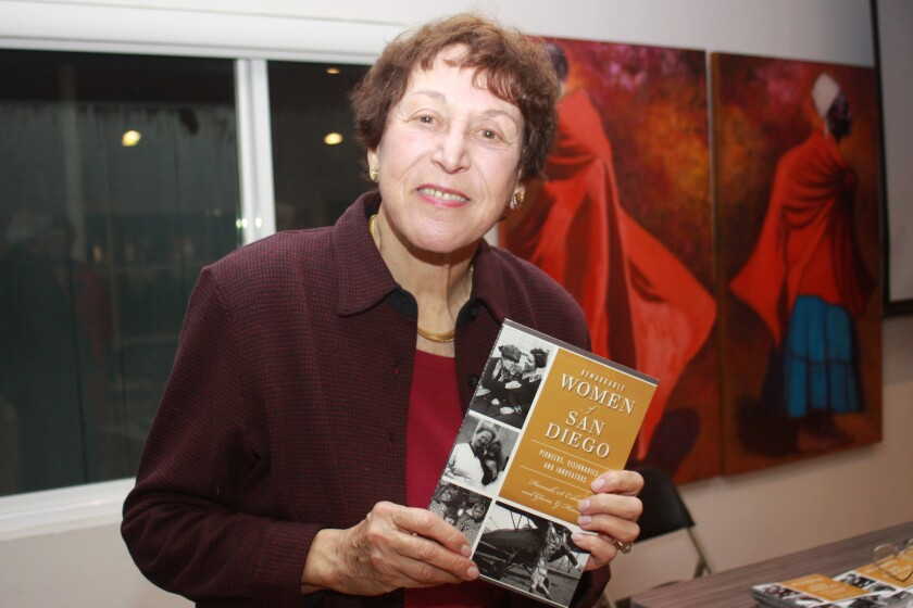 La Jollan Gloria Harris with a copy of 'Remarkable Women of San Diego: Pioneers, Visionaries and Innovators,' which she co-authored with Hannah Cohen.