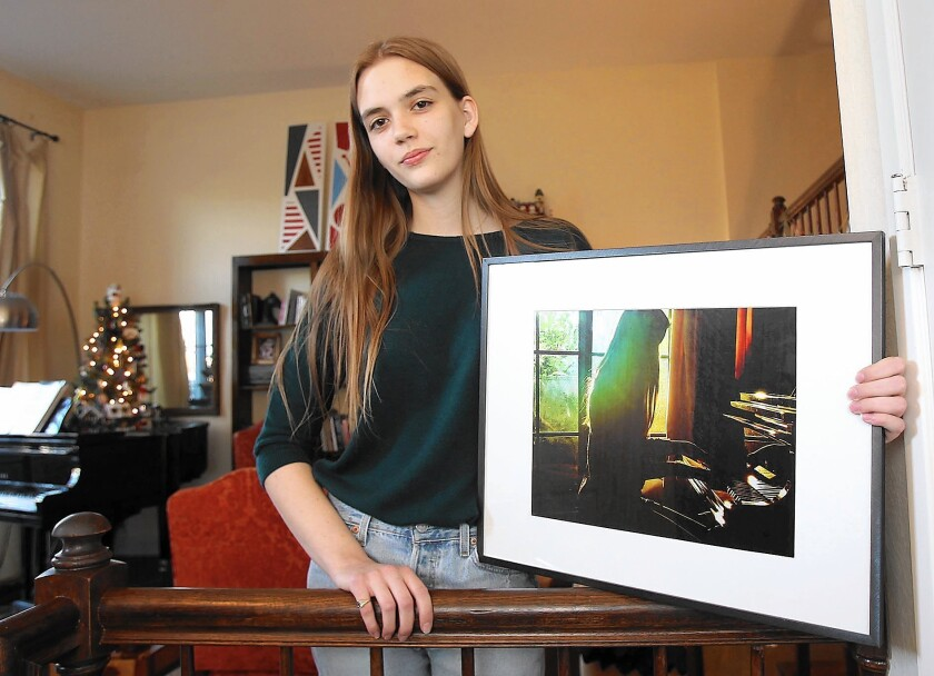Irvine student Lily McBeath holds an example of her photography. She is one of 10 students nationwide to have her artwork displayed at the Vice President's residence this month.