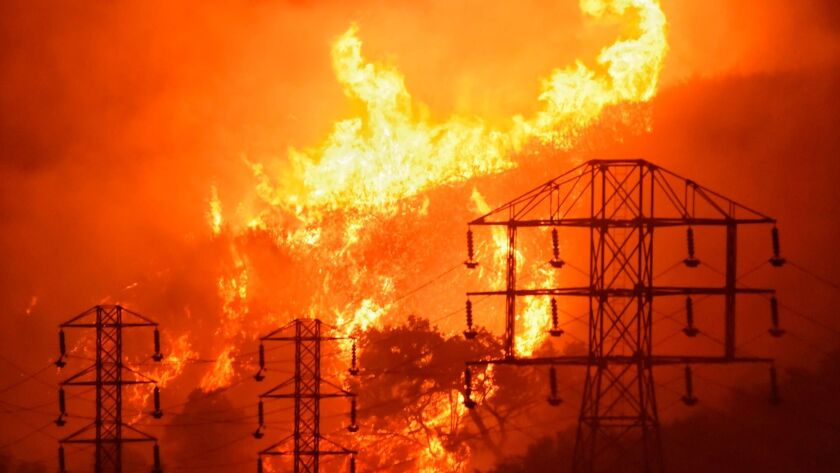 In this Dec. 16 photo provided by the Santa Barbara County Fire Department, flames burn near power lines in Sycamore Canyon near West Mountain Drive in Montecito, Calif.