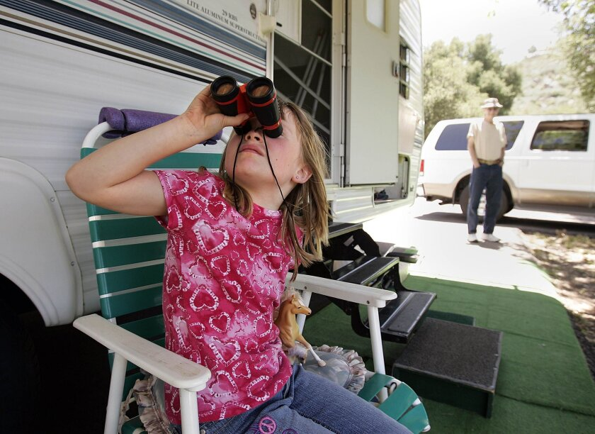 Amanda Mitchell, 8, looks through her binoculars while her grandfather Dick Jenkins stands next to his travel trailer the San Diego family will stay in this holiday weekend at Dos Picos Park in Ramona.