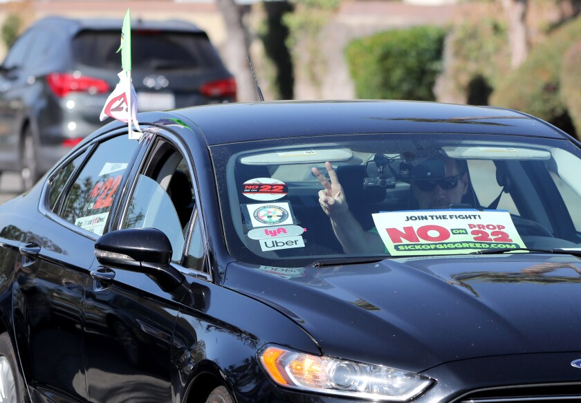 """A driver with Uber and Lyft stickers and a """"No on Prop 22"""" sign on his window pulls up at a rally in Orange."""