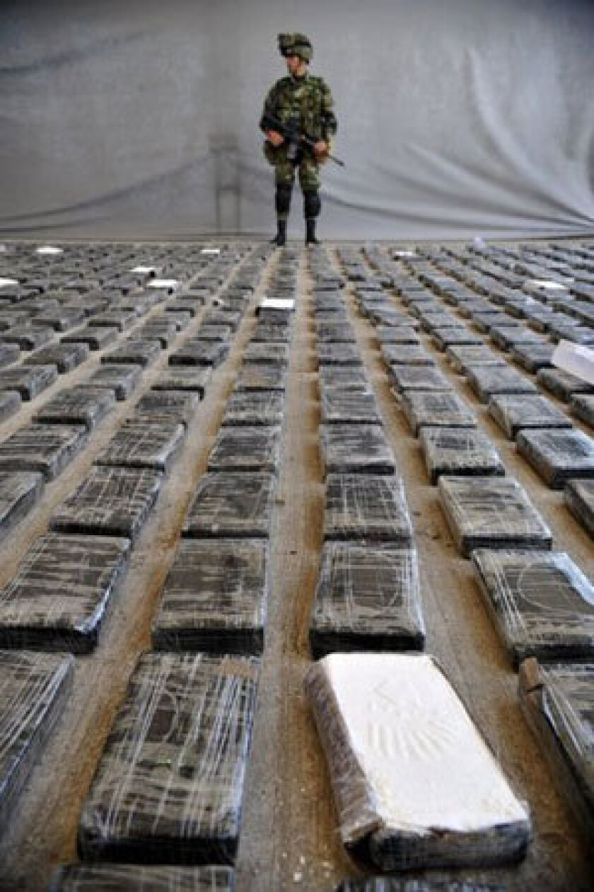 A soldier guards cocaine seized in Colombia. Research shows that cocaine takes the brakes off the user's brain reward circuitry.