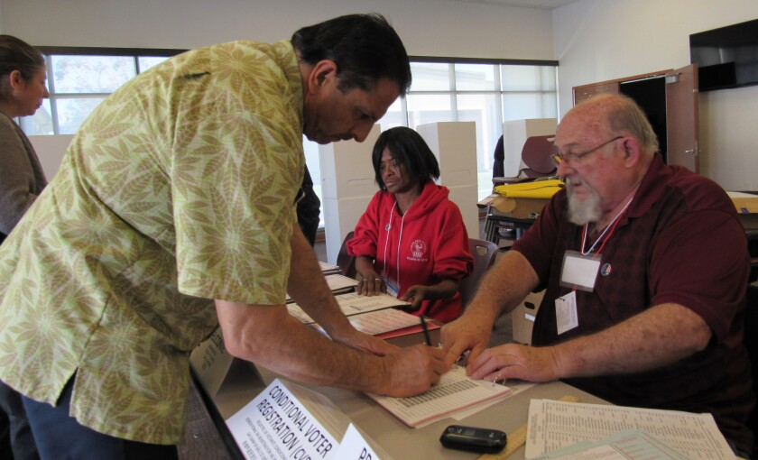 Lemon Grove resident Tomas Martinez signs his name before voting in Tuesday's election with election volunteers Terry Hoopes (right) and Jackie Spicer (center) helping with paperwork at the Lemon Grove Library.