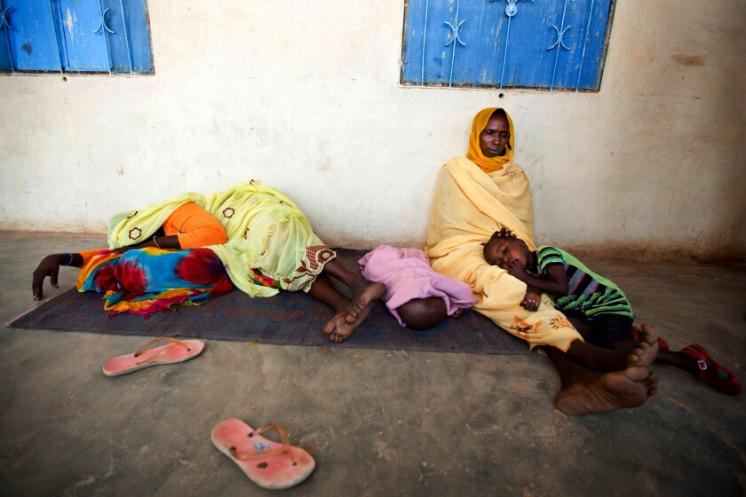 Sick women and children wait to be treated for malaria at a hospital in El Sereif village in North Darfur, Sudan.